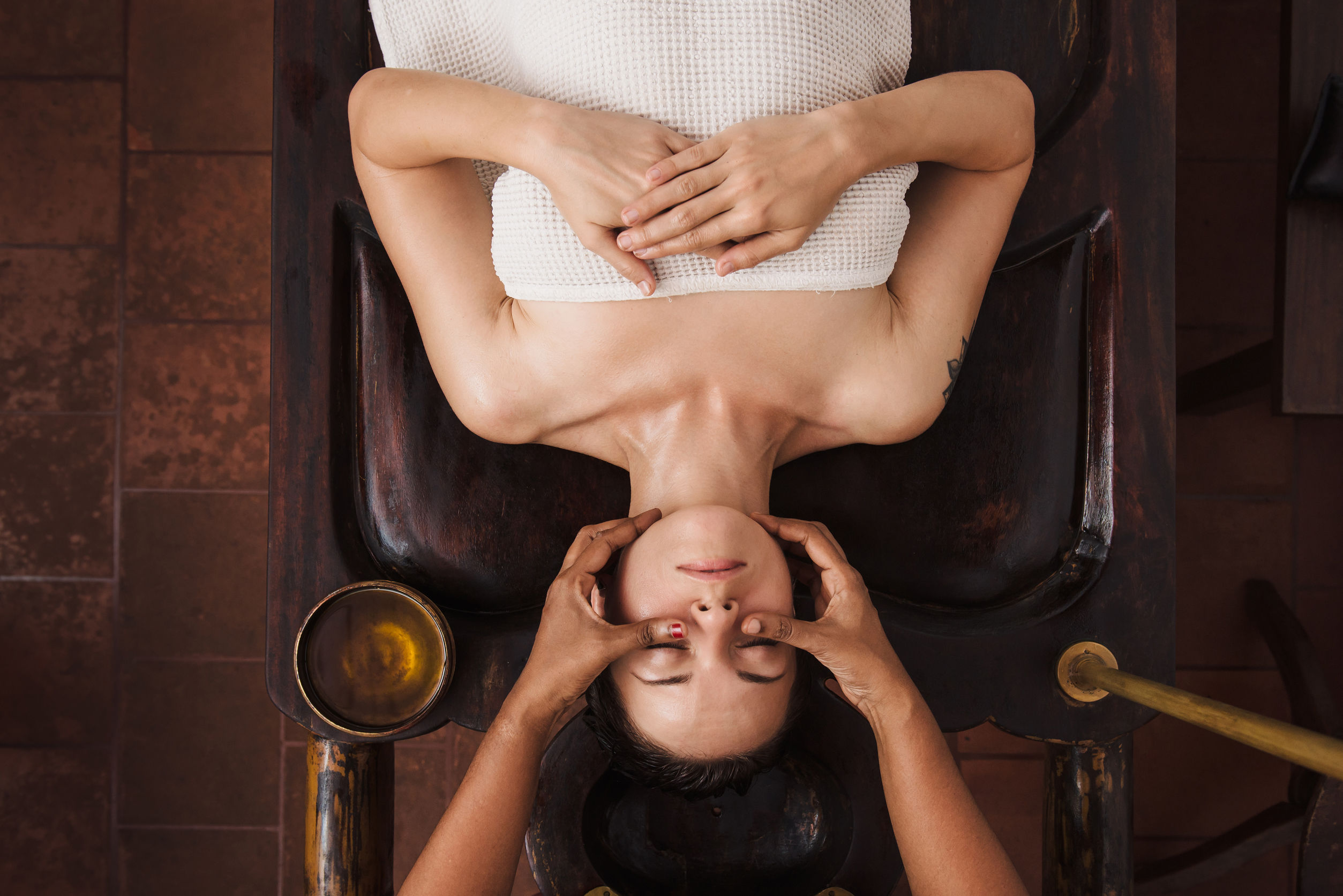 Ayurvedic face massage with oil on the wooden table in traditional style made by asian women. Top view