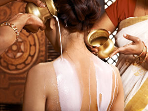 Woman having Ayurvedic buttermilk treatment.